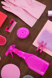 O equipamento cor-de-rosa da limpeza da cor arranjou no assoalho de madeira Imagens de Stock