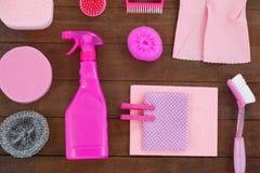 O equipamento cor-de-rosa da limpeza da cor arranjou no assoalho de madeira Fotografia de Stock Royalty Free