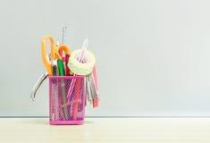 O equipamento de escritório do close up com a caixa de aço cor-de-rosa para a pena na mesa de madeira borrada e na parede de vidr Fotografia de Stock Royalty Free