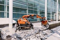 O equipamento do robô está destruindo o assoalho na zona da construção imagem de stock