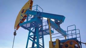 O equipamento industrial está bombeando o petróleo e o gás natural da terra, inclinação acima da vista contra o céu azul video estoque