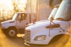 O equipamento médio transporta semi estar nas portas do armazém para carregar iluminado pelo sol fotos de stock