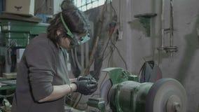O equipamento vestindo da proteção do soldador ou do ferreiro da jovem mulher que mói o aço e o ferro lisos objeta que as faíscas vídeos de arquivo