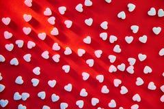O escarlate do fundo da cor com coração deu forma a comprimidos com sombras longas fotos de stock