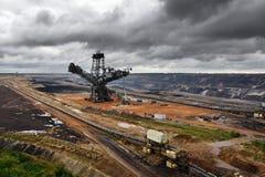 O escavador e o carvão marrom abrem - a mineração moldada imagens de stock royalty free