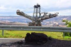 O escavador e o carvão marrom abrem - a mineração moldada imagem de stock royalty free
