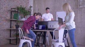 O escritório moderno, a equipe criativa nova cumprimentada no trabalho e o homem do mentor conduzem a reunião de negócios sobre o video estoque