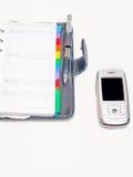 O escritório objeta - encerre o diário e um telefone de pilha Fotografia de Stock Royalty Free