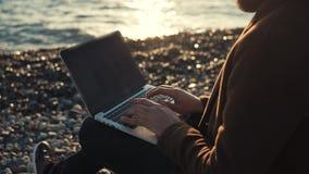 O escritor moderno está datilografando no teclado do caderno no fundo da maré do mar video estoque