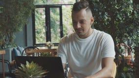 O escritor novo e ambicioso está trabalhando em seu livro usando o laptop no café vídeos de arquivo
