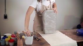 O escultor da mulher está cortando o bloco com argila cinzenta na oficina filme