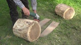 O escultor prepara a madeira do log da árvore para o trabalho de arte Casca de lixamento com ferramenta da máquina de lixar close filme