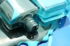 O esmalte derramado do verniz para as unhas azul e esverdeia duas garrafas no fundo azul Imagens de Stock