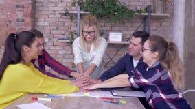 O espírito de equipe bem sucedido, os homens felizes dos trabalhadores de escritório e as mãos das mulheres empilharam juntar par