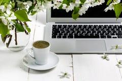 O espaço de trabalho com mão da menina no teclado e na xícara de café do portátil, as flores brancas da árvore de maçã da mola no fotografia de stock royalty free