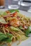 O espaguete com as bolinhas de massa do camarão servidas em uma placa branca é colocado em uma tabela preta foto de stock
