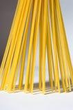 O espaguete está verticalmente sob a luz solar em um backgr branco Fotografia de Stock Royalty Free