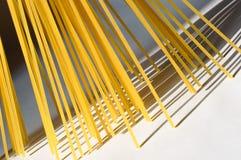 O espaguete está verticalmente sob a luz solar em um backgr branco Imagem de Stock