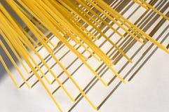 O espaguete está verticalmente sob a luz solar em um branco Imagem de Stock Royalty Free