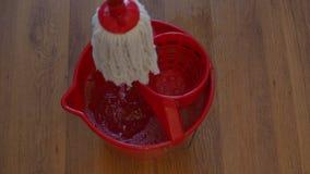 O espanador branco do algodão está espremendo na cubeta vermelha com detergente filme