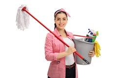 O espanador e a cubeta felizes da terra arrendada da jovem mulher encheram-se com a limpeza do PR Fotografia de Stock