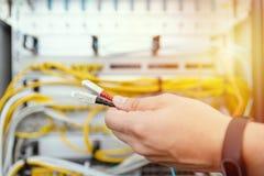 O especialista da TI conecta cabos de fibra ótica ao equipamento de rede Infraestrutura de TI fotos de stock royalty free