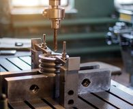 O especialista do homem verifica a ferramenta de medição com o tamanho de furar uma polia do metal e introduz uma broca na imagens de stock