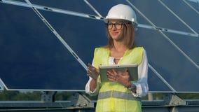 O especialista fêmea da energética está trabalhando perto de uma disposição solar e de um sorriso filme