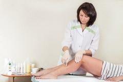 O especialista médico realiza o epilation do açúcar dos pés de uma mulher em um salão de beleza Fotos de Stock