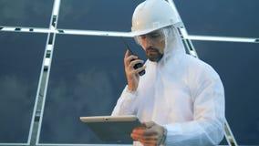 O especialista solar masculino está estando na frente de uma disposição solar e está falando em um transmissor video estoque