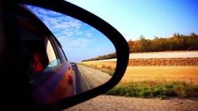 O espelho de carro com campo e o fundo da estrada apressam-se video estoque