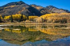 O espelho gosta da reflexão em um lago claro, refletindo montanhas com cores do outono imagens de stock