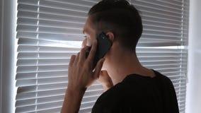 O espião, o journalista ou o detetive falam no telefone e nos relógios através das cortinas filme