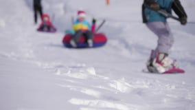 O esqui e os povos do esquiador em snowboards montam abaixo da inclinação na estância de esqui no inverno das montanhas filme