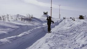O esqui e os povos do esquiador em snowboards montam abaixo da inclinação na estância de esqui no inverno das montanhas vídeos de arquivo