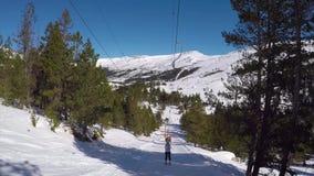 O esquiador aumenta acima no elevador de esqui, rolando na neve, cercada por florestas filme
