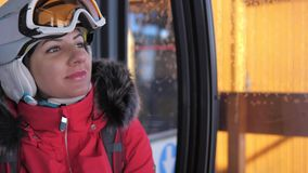 O esquiador bonito de sorriso da mulher do close-up aumenta sentando-se em Ski Lift Cable Car filme