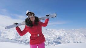 O esquiador bonito de sorriso da mulher está em um montanhês, guardando esquis em seus ombros vídeos de arquivo