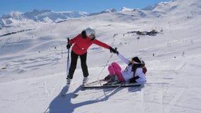 O esquiador da mulher ajuda o outro a aumentar a seus pés após a queda em Ski Slope vídeos de arquivo
