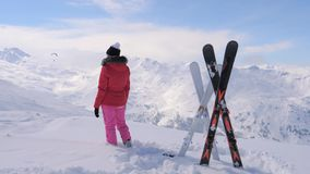 O esquiador da mulher está na parte superior da montanha e olha afastado filme
