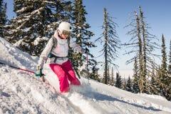 O esquiador da mulher monta através da neve do pó às montanhas Freeride dos esportes de inverno Fotografia de Stock Royalty Free