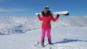 O esquiador da mulher que está na montanha da inclinação, guardando entrega Ski On Shoulders video estoque