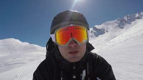 O esquiador de Selfie Portait acelera rapidamente o esqui em declive em montanhas do inverno vídeos de arquivo