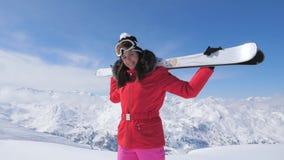 O esquiador de sorriso da mulher está em uma montanha máxima, guardando esquis em seus ombros video estoque