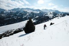 O esquiador desce através da neve contra o contexto das montanhas imagem de stock