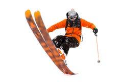 O esquiador do atleta no terno preto alaranjado faz o truque na parte de trás dos esquis foto real feita nas montanhas foto de stock royalty free