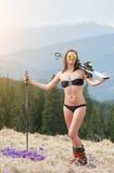 O esquiador fêmea feliz está apreciando a mola morna, o roupa de banho vestindo, as botas e os óculos de sol Foto de Stock