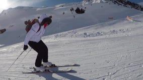 O esquiador nas montanhas em uma inclinação delicada empurrou suas varas para o esqui para baixo filme
