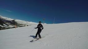 O esquiador nas montanhas no inverno rola para baixo uma trilha em declive de torção rápida filme