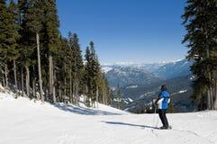 O esquiador parou na fuga, olhando montanhas Imagem de Stock Royalty Free
